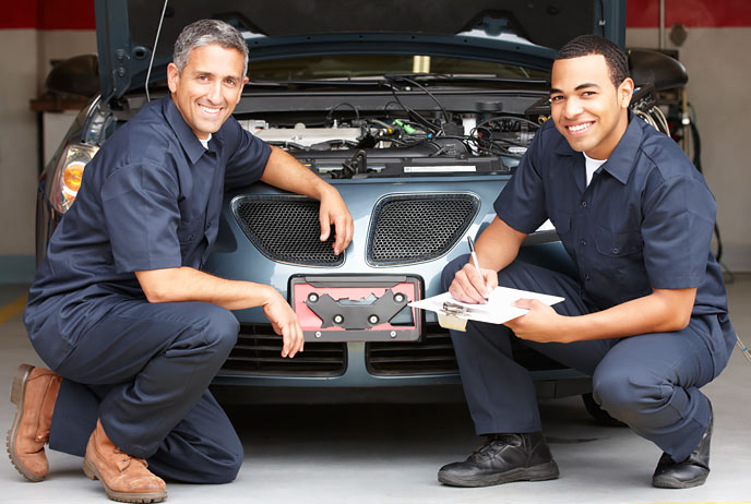 Image of two auto mechanics in front of a car